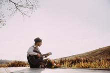 Young Man Playing Guitar Sitti...