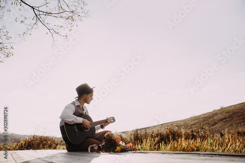 Young man playing guitar sitting on the bank of a mountain river on a background of rocks and forest Wallpaper Mural