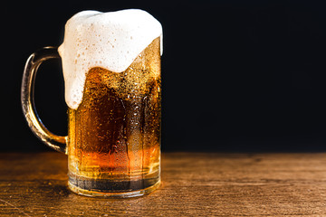 Cold beer with foam in a mug, on a wooden table and a dark background with bl...