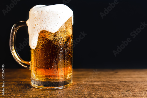 Fotografia  Cold beer with foam in a mug, on a wooden table and a dark background with blank space for a logo or text