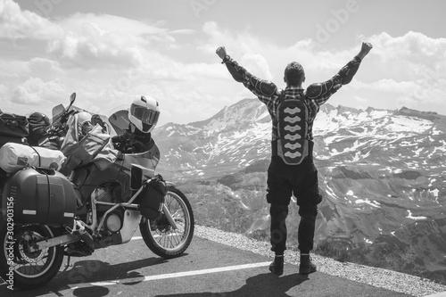 Podróżujący motocyklem z tyłu jest szczęśliwy, że przybył do celu. Podbijając szczyt góry, przełęcz Grossglockner, rowerzysta ubrany w ochronną kurtkę zbroję czarno-białą. Austria
