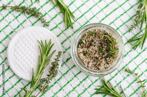 Obraz Homemade herbal scrub (foot soak or bath salt) with rosemary, thyme, sea salt and olive oil. Natural skin and hair care. DIY beauty treatments and spa recipe. Top view, copy space   - fototapety do salonu