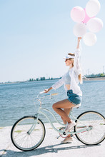 Side View Of Smiling Blonde Girl Riding Bike With Balloons Near River In Summer