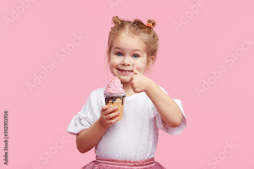 Cute child girl with pleasure eats tasty ice-cream on a pink studio background. Licks with closed eyes. The concept of baby food and a happy childhood