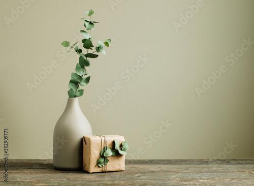 Fototapeta Eucalyptus branch in a vase on the rustic wooden table obraz