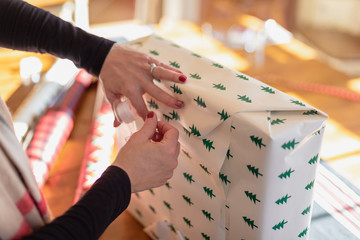 woman wrapping and taping Christmas present at home