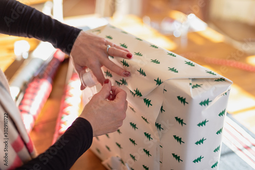 Photo  woman wrapping and taping Christmas present at home