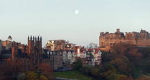Sunrise Over Edinburgh Castle. The First Sun Rays Hit The Iconic Buildings Of The Old Town While A Full Moon Is Still Showig In The Early Morning Sky