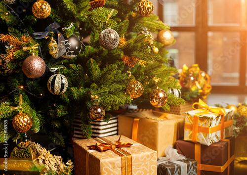 Fototapeta Close-up of a Christmas tree decorated with gold balls. Under the Christmas tree a large number of Christmas gifts. Christmas holiday concept obraz