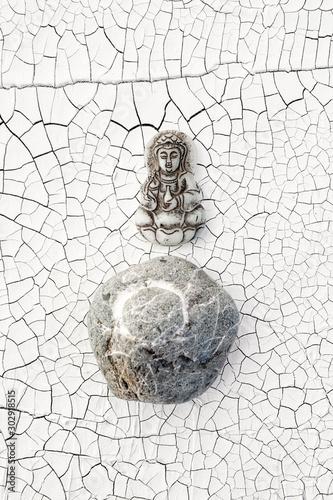 Photo Buddha and Enso Circle Stone on cracked white background.