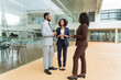 Multiethnic team discussing project near office building. Business man and women standing at outdoor glass wall, talking to each other. Corporate meeting concept