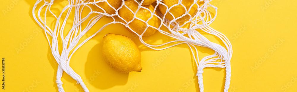 Fototapeta top view of fresh ripe whole lemons in eco string bag on yellow background, panoramic shot