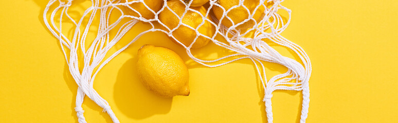 top view of fresh ripe whole lemons in eco string bag on yellow background, p...
