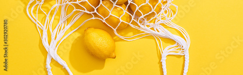 Fototapeta top view of fresh ripe whole lemons in eco string bag on yellow background, panoramic shot obraz