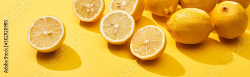 ripe-cut-and-whole-lemons-on-yellow-background-panoramic-shot