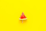 Fresh watermelon on stick for fruit ice cream on yellow background top view