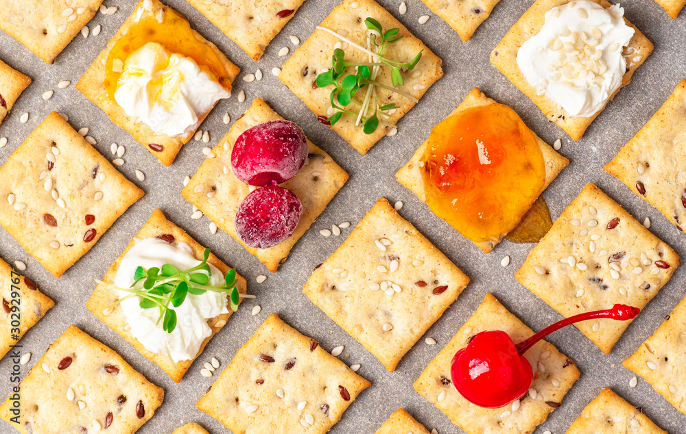 Fototapeta Homemade freshly baked crackers with flax and sesame seeds with various serving options are laid out on baking paper, top view. Crackers with seeds, ricotta, jam, berries and microgreens, flat lay.