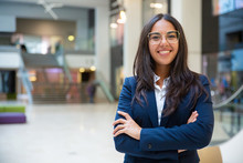 Happy Successful Businesswoman Posing In Office Hall. Young Latin Woman Wearing Formal Suit And Glasses, Standing For Camera With Arms Folded, Smiling. Business Portrait Concept