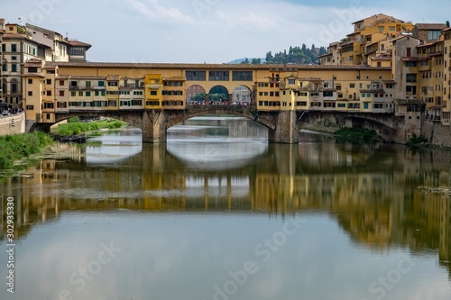Ponte Vecchio bridge in the foreground of high buildings reflected in the lake in Florence, Italy