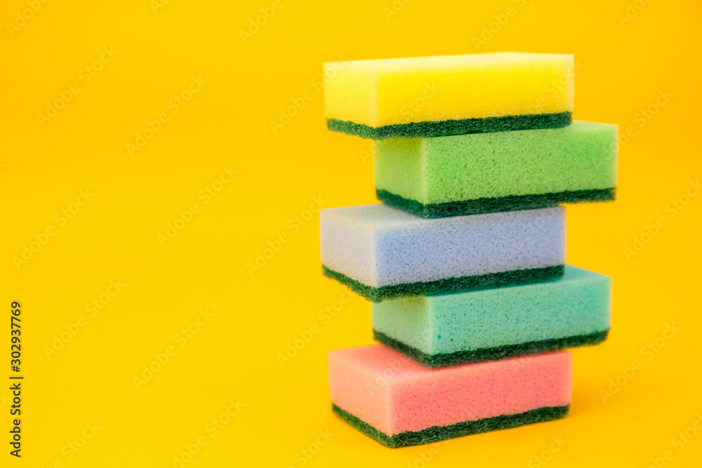Fototapeta Multicolored sponges for cleaning folded pyramid on a yellow background. Space for text