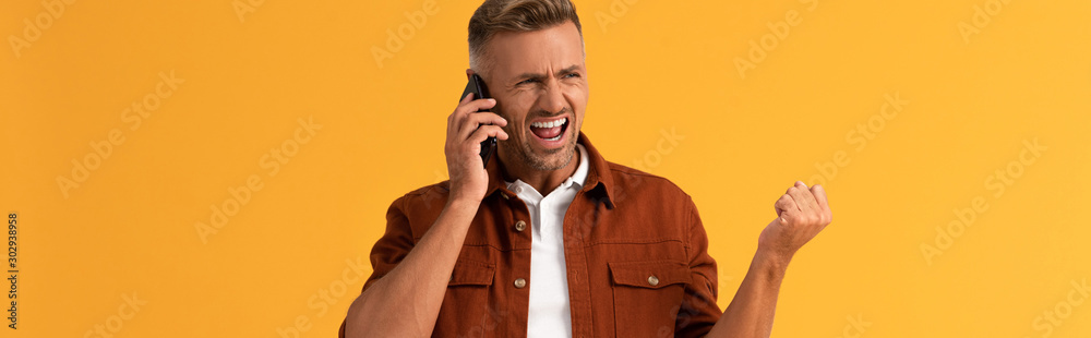 Fototapety, obrazy: panoramic shot of angry man screaming while talking on smartphone isolated on orange