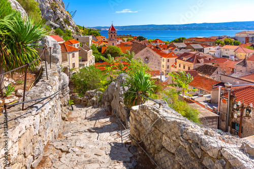 Sunny red roofs, Old city street with stone stairs and Church of St Michael in town and port Omis, popular tourist spot in Croatia