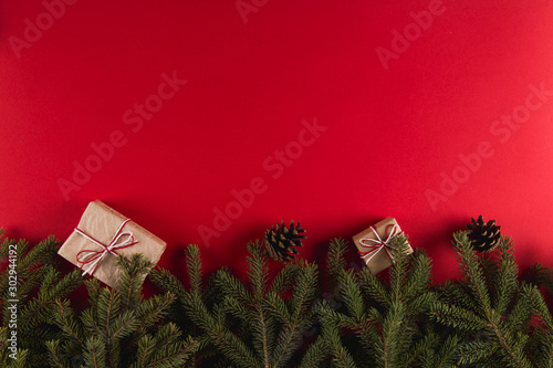 Cuadros en Lienzo  Christmas tree branches, gifts and pine cones on a red background, Christmas concept, greeting card copy space