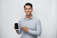 Pleased Happy Young Asian Man Holding Smartphone Pointing At Cellphone Screen As Showing Awesome New Phone