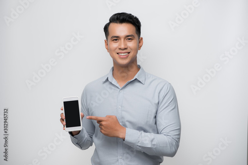 Cuadros en Lienzo  Pleased happy young asian man holding smartphone pointing at cellphone screen as