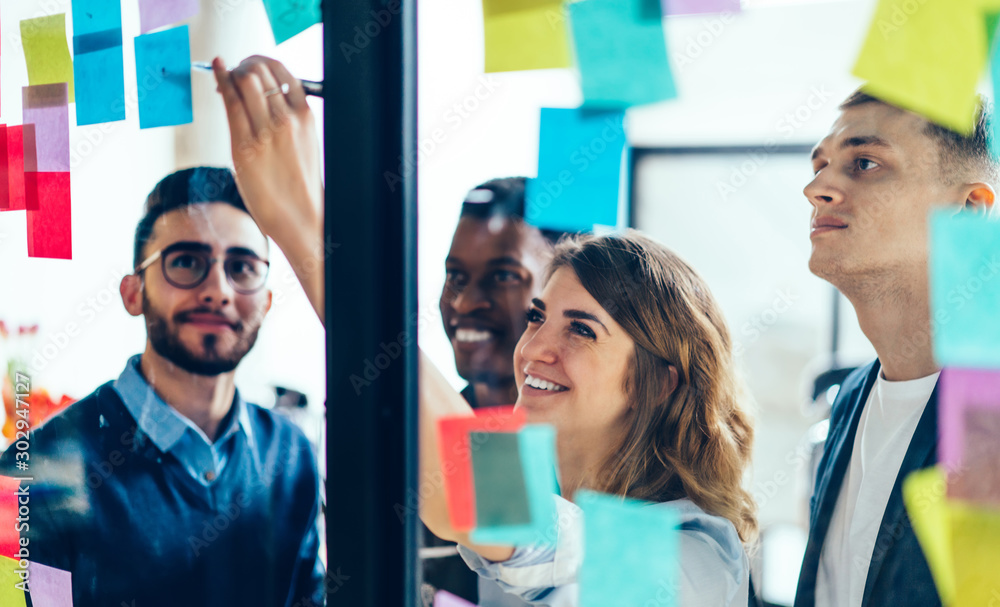 Fototapeta Smiling cheerful female entrepreneur writing funny information on paper stick while enjoying cooperation with male entrepreneur colleagues, multicultural people creating new strategy for proud ceo