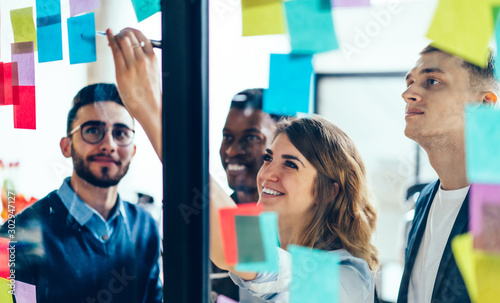 Obraz Smiling cheerful female entrepreneur writing funny information on paper stick while enjoying cooperation with male entrepreneur colleagues, multicultural people creating new strategy for proud ceo - fototapety do salonu