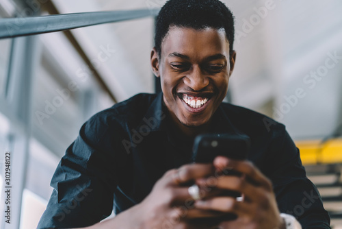 Cheerful excited black man reading positive news in social network using 4g conn Tablou Canvas