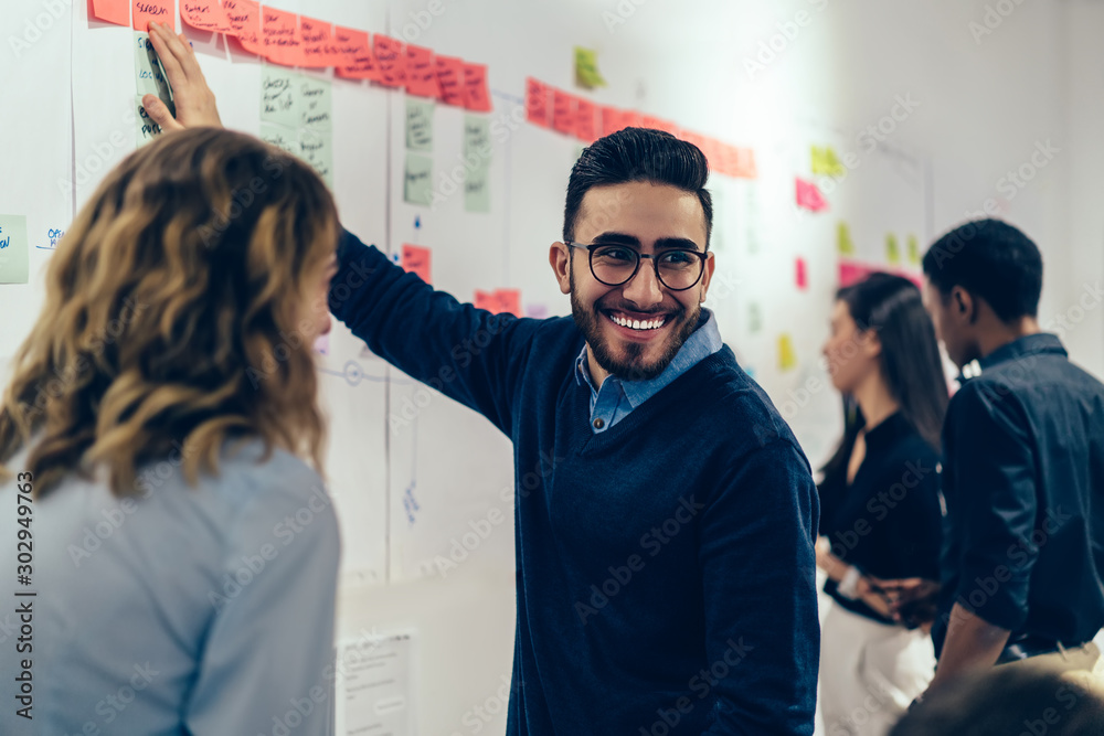 Positive young man laughing while collaborating with colleagues on creating presentation using colorful stickers for productive work in office.Male and female students having fun during workshop