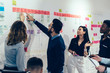 Team of multicultural young people pointing on wall with glued colorful paper notes with foreign words during productive lesson.Diverse group of male and female employees in formal wear using stickers