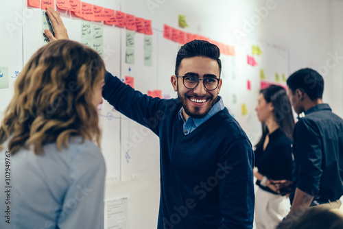 Fotomural  Positive young man laughing while collaborating with colleagues on creating presentation using colorful stickers for productive work in office