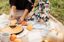 Young Mom With A Little Cute Daughter At An Autumn Picnic Cut A Pumpkin Tart.