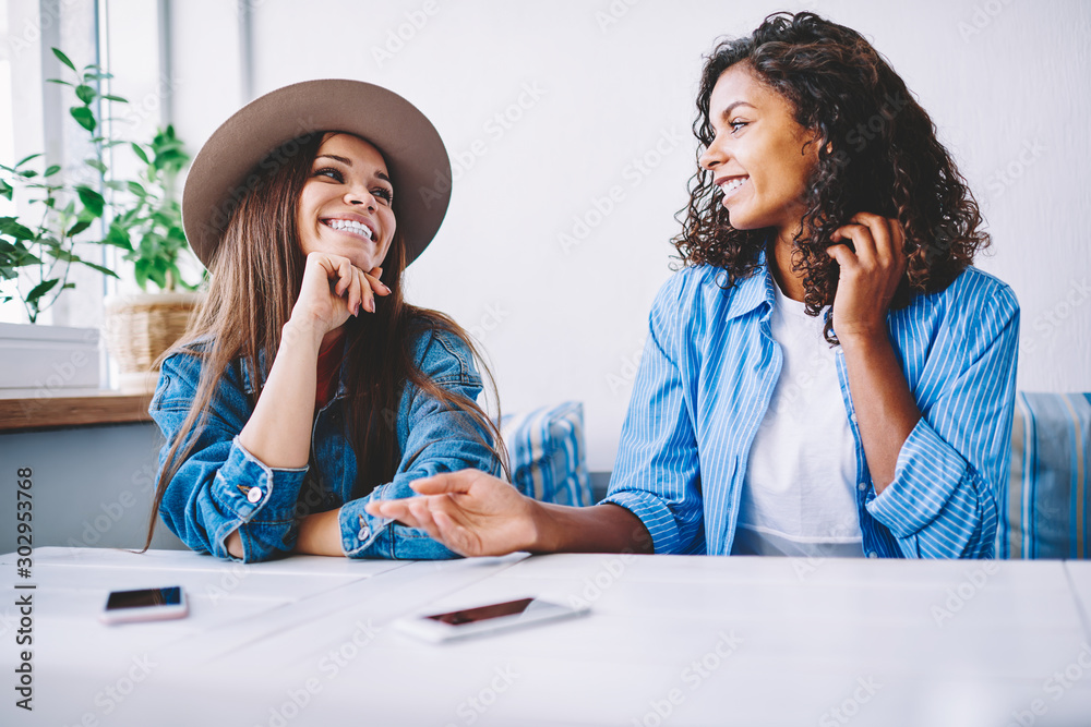 Fototapeta Cheerful female best friends in stylish casual wear having fun on meeting in cafe interior resting together, happy hipster girls communicating and joking while sitting in coffee shop during free time