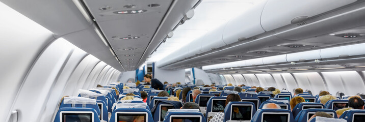 Cabin of modern aircraft with passengers on seats