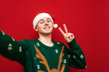 Portrait Of A Cheerful Boy In A Christmas Hat And Sweater On A Red Background, Looks Into The Camera And Shows A Gesture Of Peace. Happy Young Man Making Christmas Selfie On Bright Background.Isolated