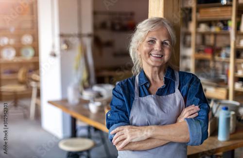 Obraz Portrait of senior female pottery artist in her art studio - fototapety do salonu