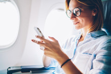 Attractive Female Passenger Of Airplane Read News From Networks Via Smartphone And Wifi On Board,young Woman Sending Message On Phone Traveling By Plane In First Class Connecting To Wireless On Phone