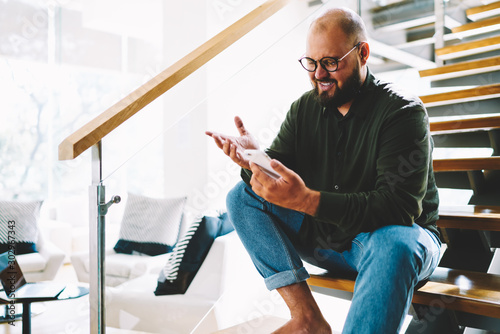 Fotografía  Cheerful bearded blogger in eyewear watching online lifestream on smartphone via home wifi sitting on wooden stairs in apartment