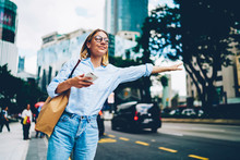 Smiling Female Traveler In Trendy Casual Wear Raising Hand Calling Taxin Standing On Road In City On Urban Background, Young Woman Waiting For Cab For Transporting In Megalopolis Waving On Avenue