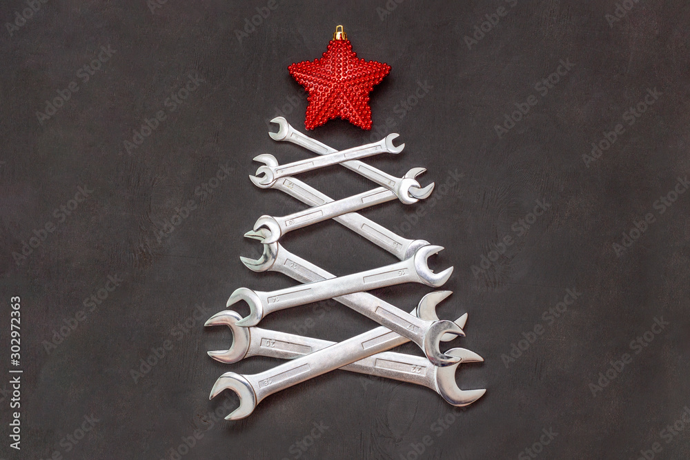 Fototapeta Christmas tree made of tools. Wrenches spanners on black background. Industrial greeting card and happy new year creative concept.