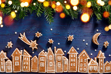 Christmas Background, Christmas Gingerbread  Town, Image Created From Gingerbread Cookies Houses, Fresh Yew Branches, Gingerbread Stars  And Twinkling Lights On A Dark Blue  Background.