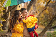 Happy Parents And Daughter With Rainbow Colored Umbrella Under Rain On Nature