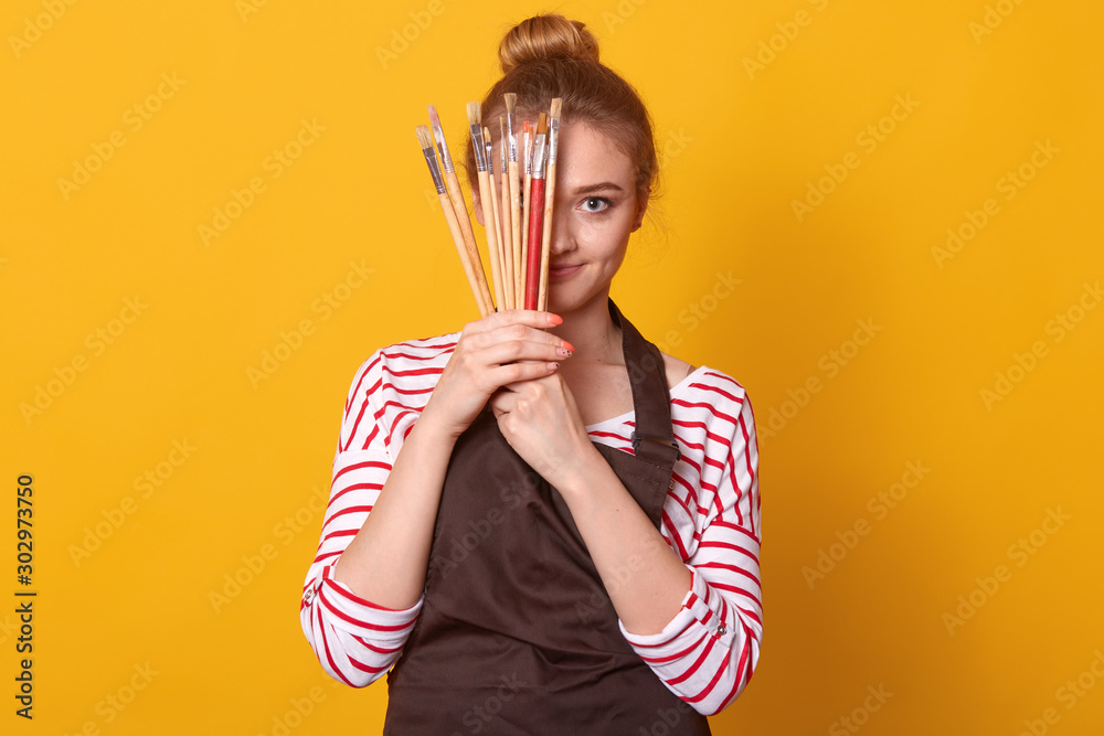 Fototapety, obrazy: Picture of delighted tender cute young lady holding lots of brushes in both hands, covering half of face with art equipment, wearing striped sweatshirt and brown apron. People and free time concept.