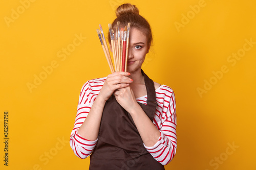 Cuadros en Lienzo  Picture of delighted tender cute young lady holding lots of brushes in both hands, covering half of face with art equipment, wearing striped sweatshirt and brown apron