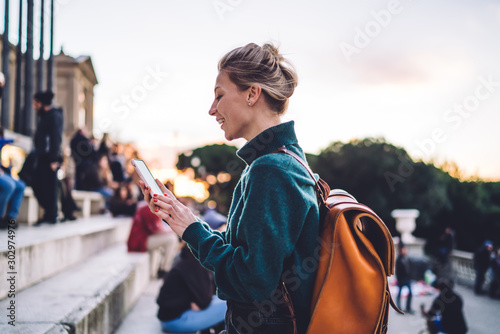 Fotografía  Side view of millennial female tourist in casual apparel chatting at online mobi