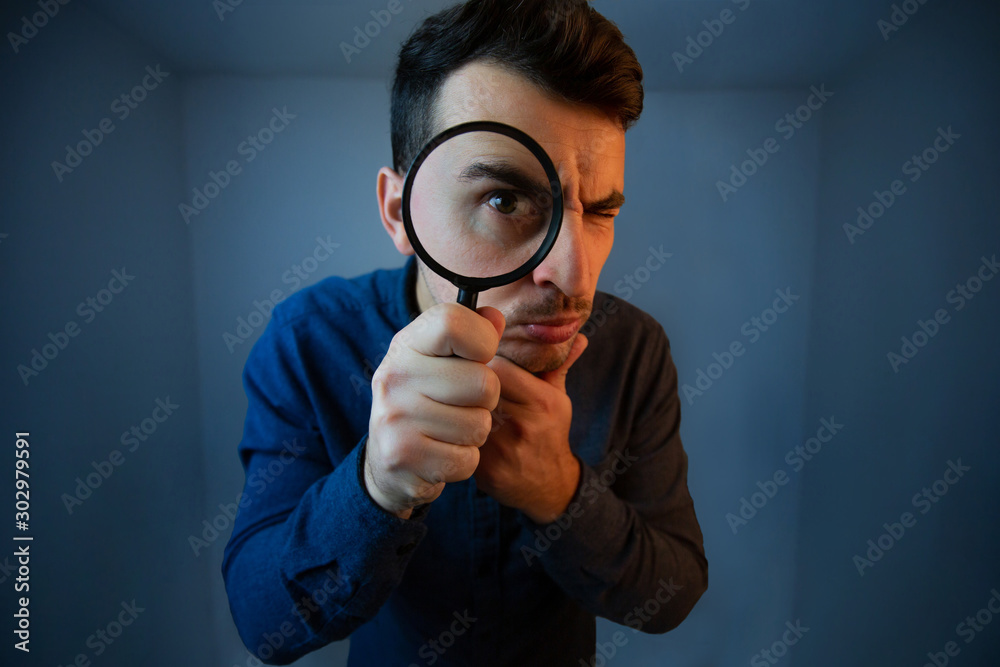 Fototapeta Surprised Young man student holding magnifying glass looking to camera with a pensive emotion isolated over grey  background. Science and curiosity concept.